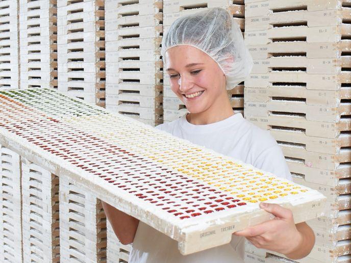 Funcionária a examinar figuras de goma de frutas recém-moldadas