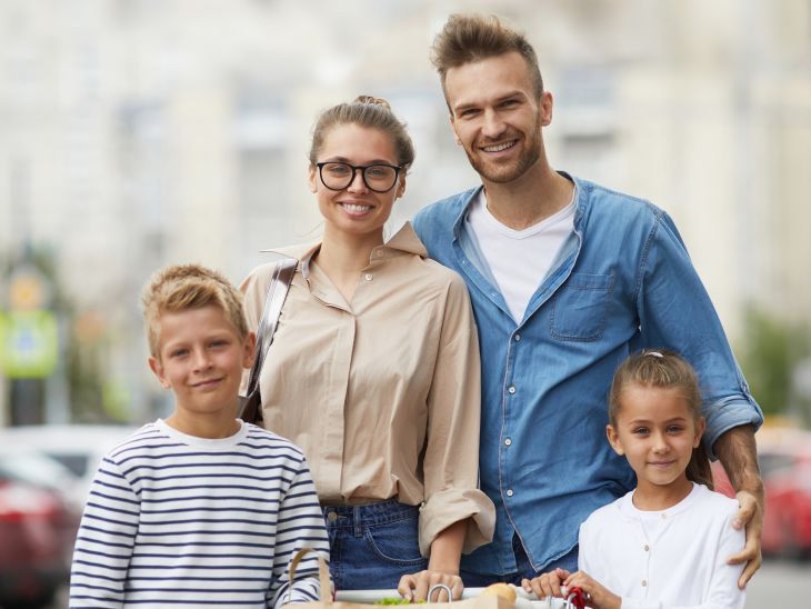 Семья стоит с тележкой для покупок на автостоянке перед супермаркетом