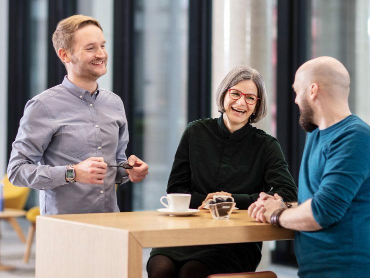 Drie medewerkers praten in het cafetaria