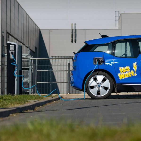 şarj istasyonunun önünde HARIBO markalı mavi elektrikli araba