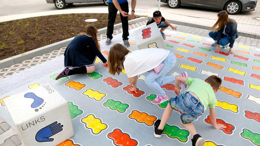 Kinder spielen Twister auf Goldbären-Spielfläche