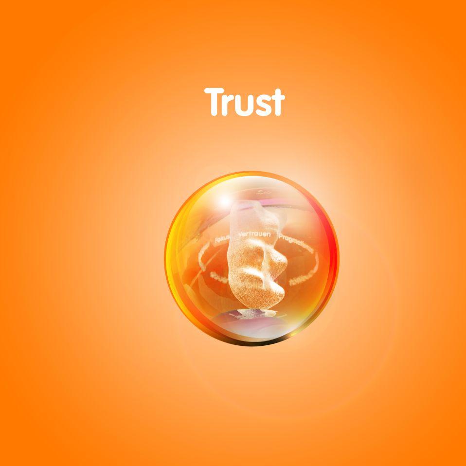 Изображение золотого мишки в прозрачном шаре на оранжевом фоне с текстом «Доверие»