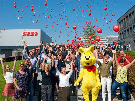 Funcionários da HARIBO com ursinho de ouro de tamanho natural na sede de Grafschaft