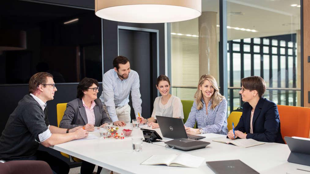 Mitarbeiter sitzen an Besprechungstisch in einem Seminarraum