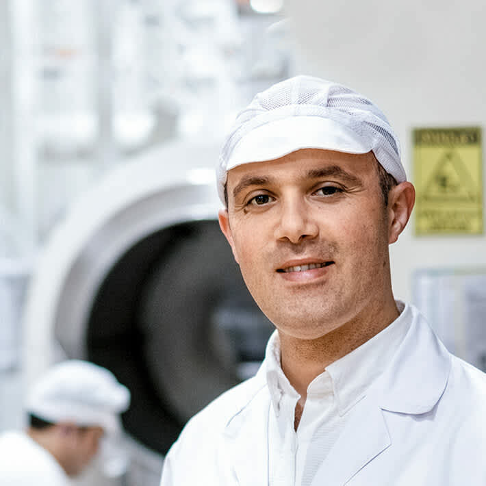 Employee standing in front of production line.