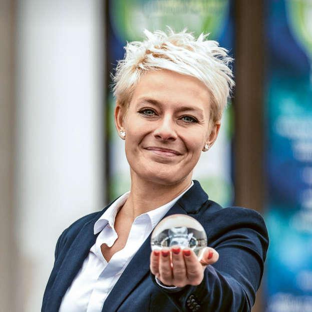 Сотрудница с улыбкой протягивает маленький стеклянный шар к объективу
