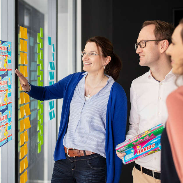 HARIBO employee in front of a wall with colourful Post-its