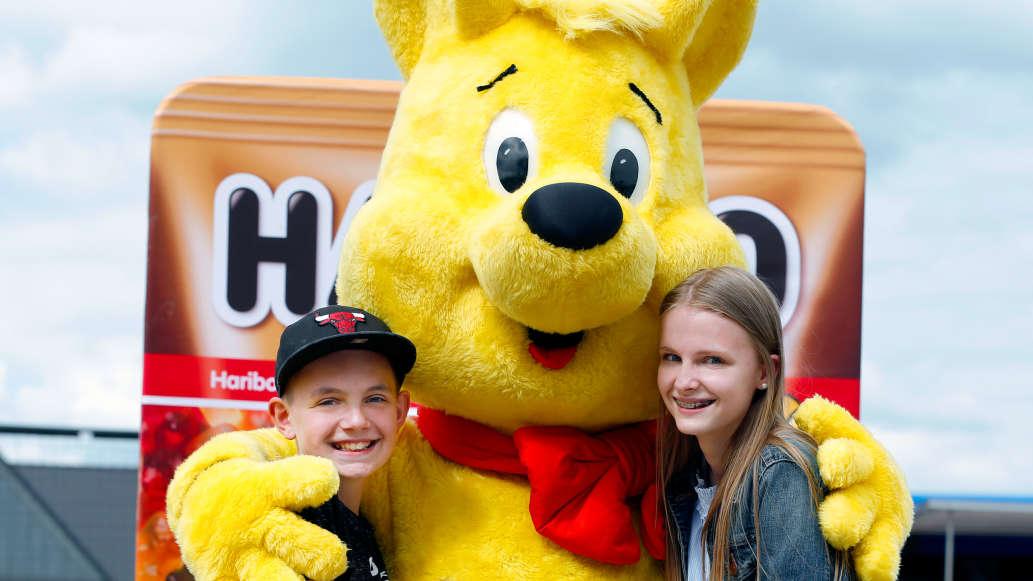 Lebensgroßer Goldbär umarmt Kinder