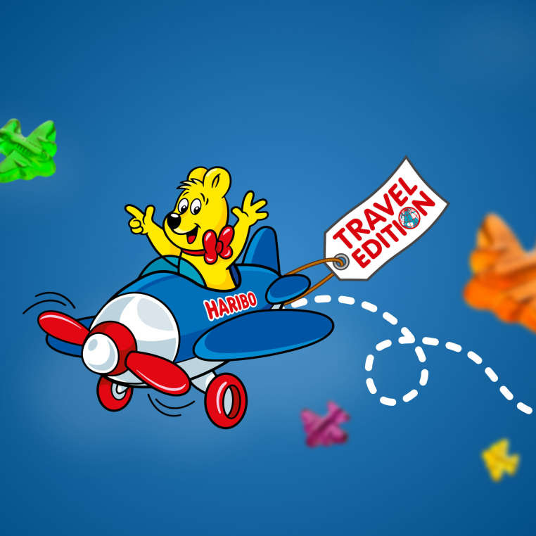 """Goldbear in a plane with a hanger saying """"Travel Edition"""""""