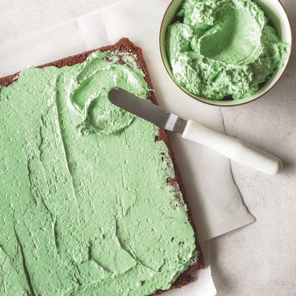Grüne Buttercreme wird auf dem Kuchen verteilt