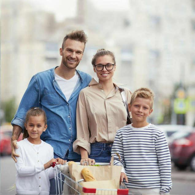 أسرة تقف مع عربة التسوق أمام ساحة انتظار للسيارات لسوبر ماركت