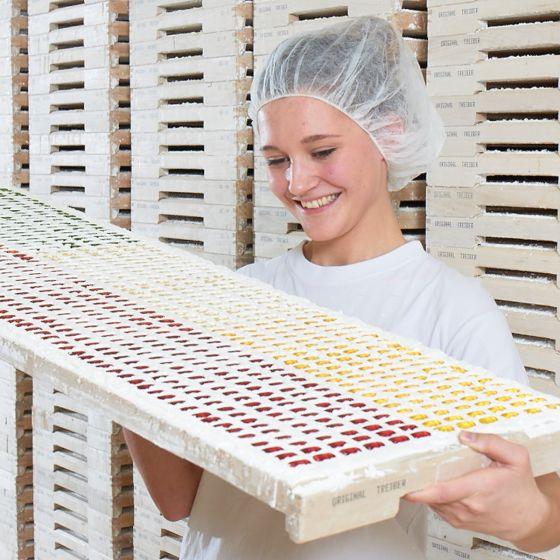 Employee examining finished fruit gummy figures