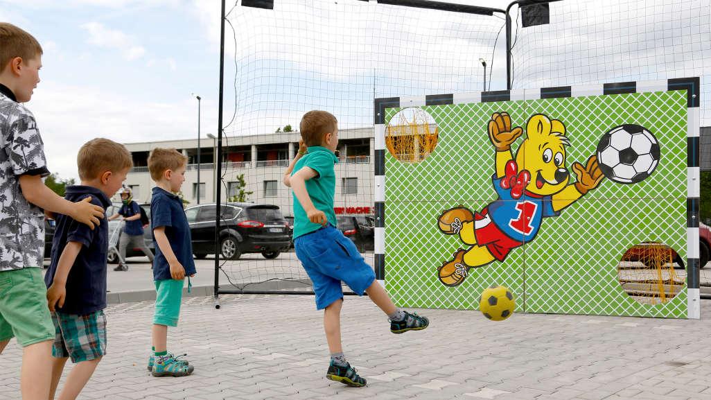 Kinder schießen auf eine Torwand mit Goldbär-Motiv