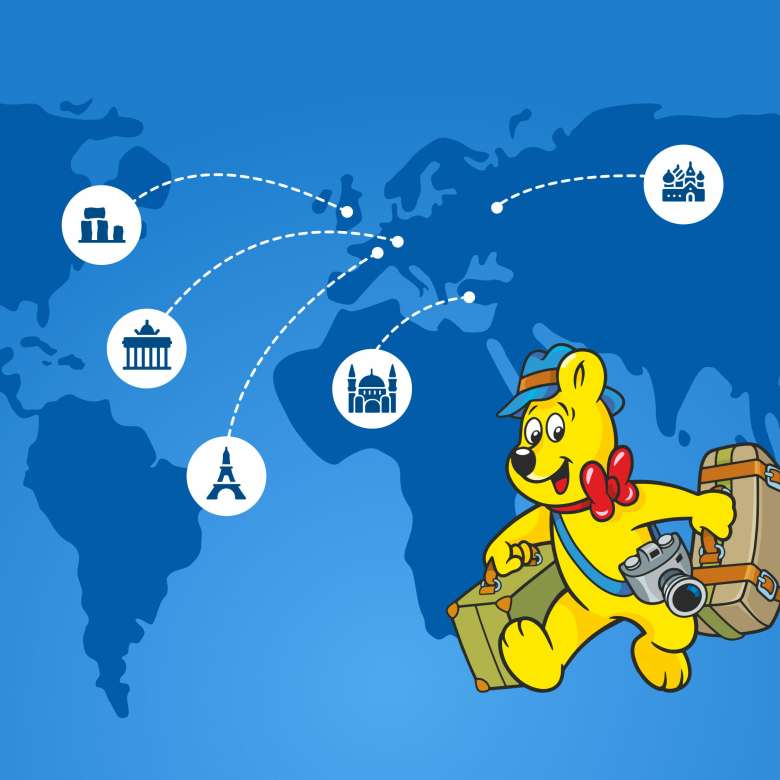 Goldbear with travel suitcases on a map showing well known sights: eifel tower, berlin gate, jesus statue brazil