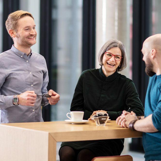 Drei Mitarbeiter unterhalten sich in der Cafeteria