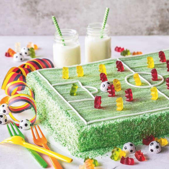 Rechteckiger Kuchen mit grünem Spielfeld aus Pasta Frutta und Goldbären als Spielern