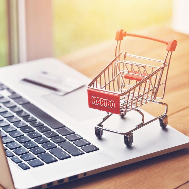 Laptop mit rotem Miniatur-Einkaufswagen und HARIBO-Logo