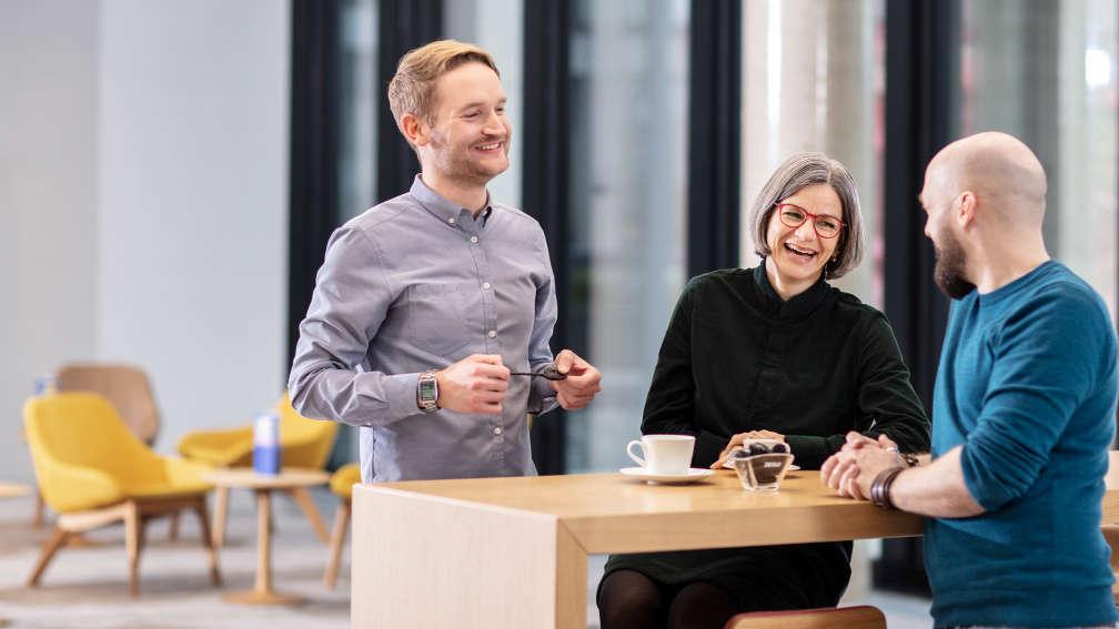 Drei HARIBO-Mitarbeiter unterhalten sich lachend in der Cafeteria
