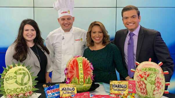 Head of Corporate Communications, Lauren Triffler, Chef and newscasters pose with watermelon sculptures in ABC7 Chicago Studio