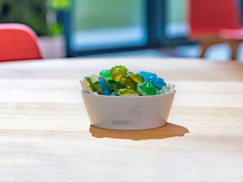Bunte HARIBO Produktstücke liegen in einer Schale auf einem Tisch