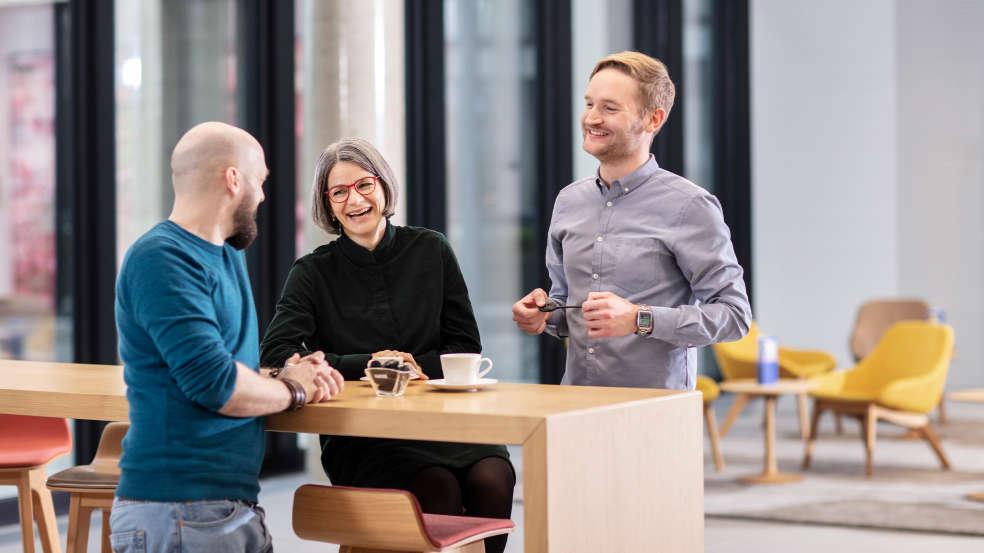 Mitarbeiter lachen zusammen beim Austausch von Süßwaren
