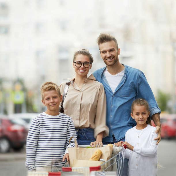 Familie steht mit Einkaufswagen vor Supermarkt Parkplatz