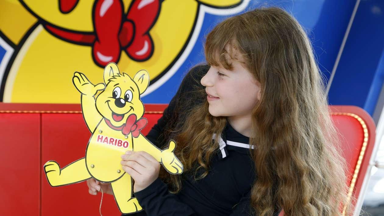 Ein Mädchen hält einen Goldbär Hampelmann