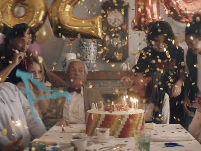 Un groupe de personnes de tous âges autour d'un gâteau Ours d'or