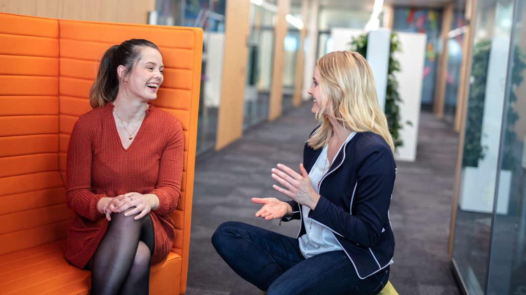 Junge Mitarbeiterin im Gespräch mit einer erfahrenen Mitarbeiterin