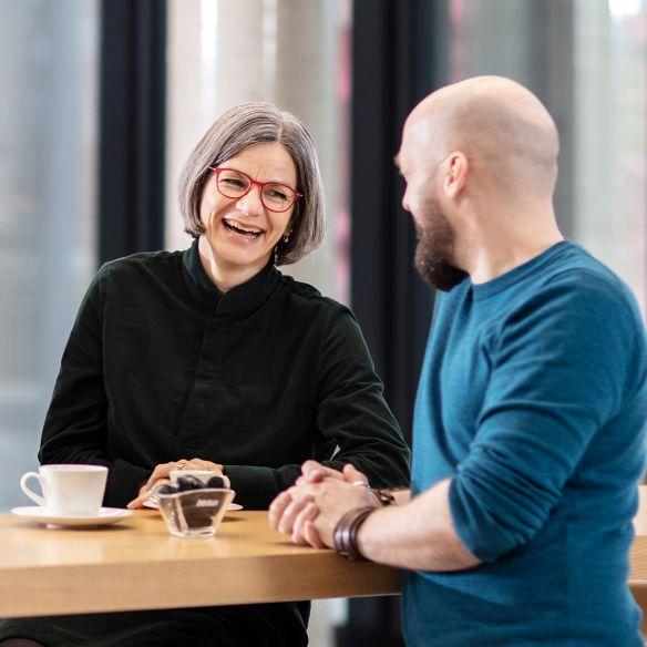 Zwei HARIBO-Mitarbeiter unterhalten sich lachend