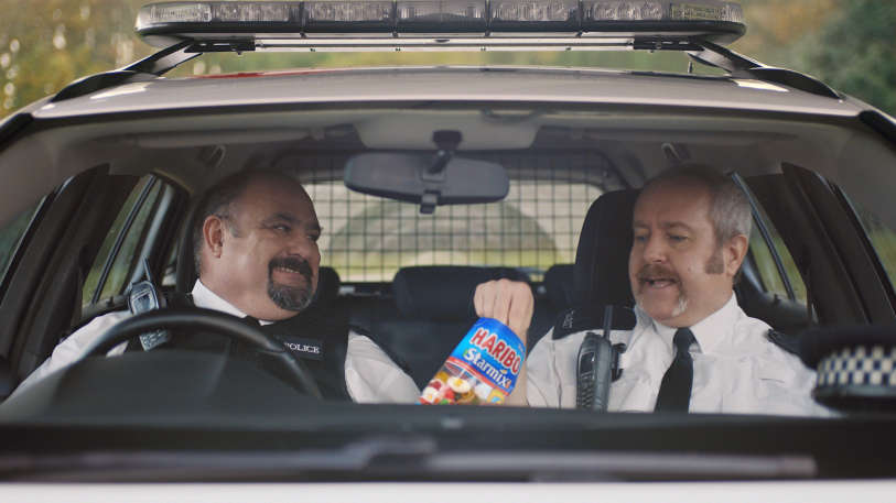 Two police men in their car eating HARIBO starmix