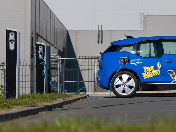 blaues Elektroauto mit HARIBO Branding vor Ladestation