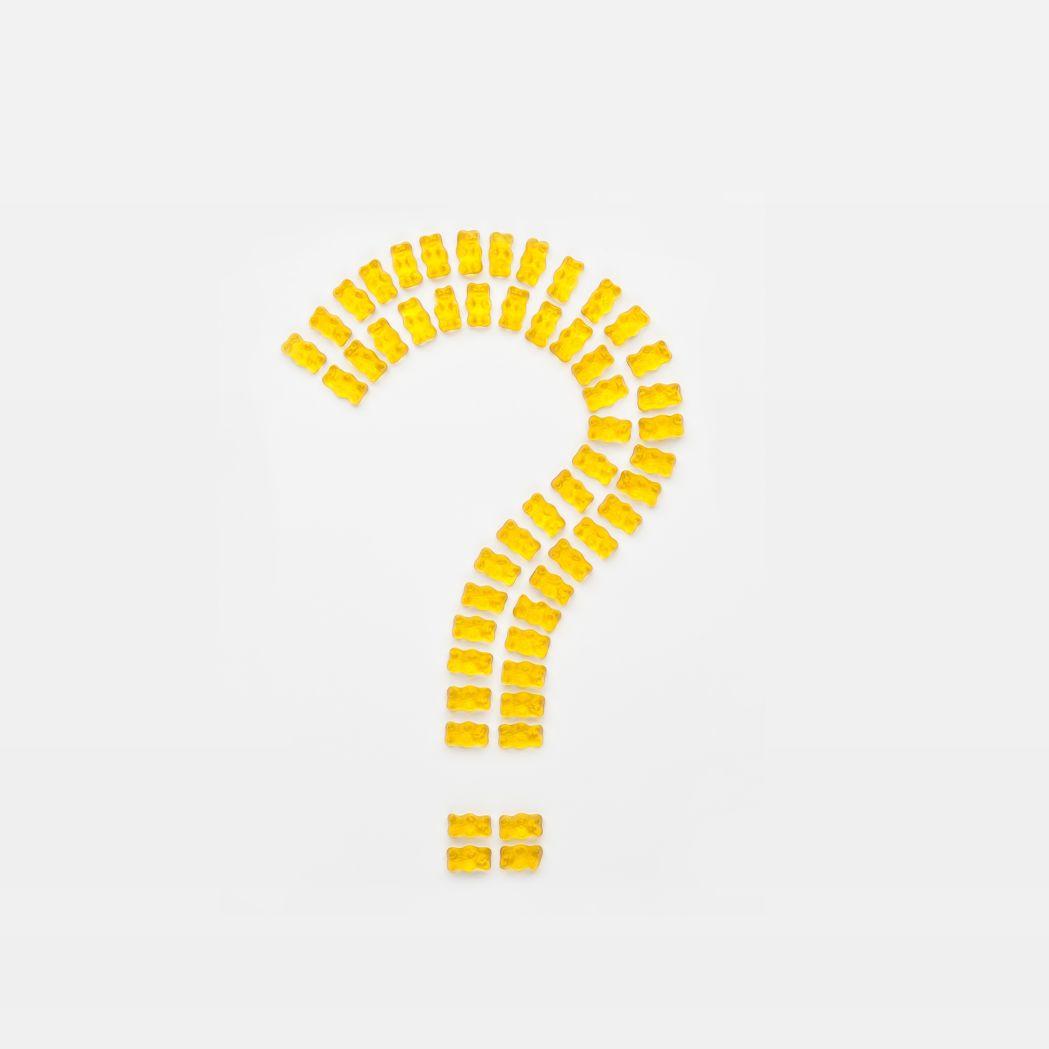 Mit gelben Goldbären gelegtes Fragezeichen auf hellem Hintergrund
