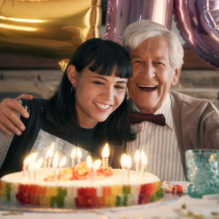 Grandfather and granddaughter in front of a birthday cake made of HARIBO Goldbears