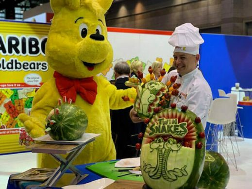 Goldbear and chef with watermelon sculptures at Sweets and Snacks Expo