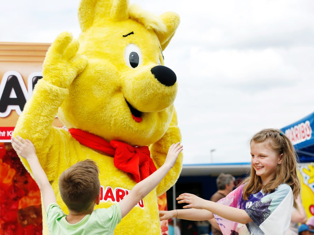 Lebensgroßer Goldbär tanzt mit zwei Kindern