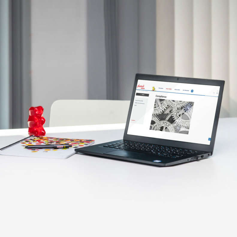 Laptop with a large red Goldbear on a table in an office