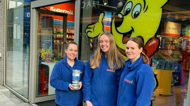Three women with charity tin in front of HARIBO store