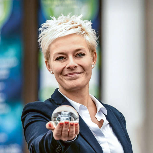 موظفة مبتسمة تثبت كرة زجاجية صغيرة في الكاميرا