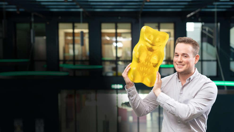 employee holding big yellow gummi bear