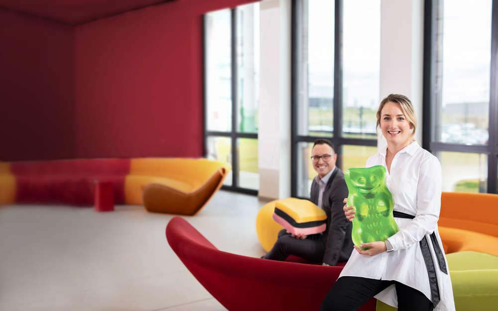 Lächelne Mitarbeiter halten übergroße Produktstücke in den Händen