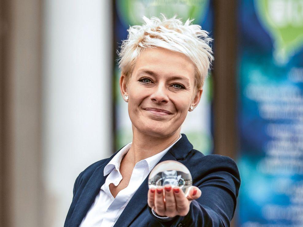 Lächelnde Mitarbeiterin hält kleine Glaskugel in die Kamera